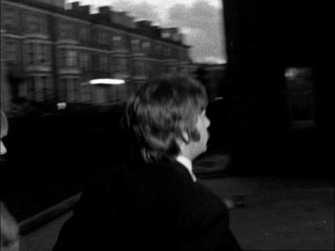 brian epstein memorial service:; england: london: swiss cottage synagogue: ext / dusk: john lennon from car l-r; pan back as paul mccartney from car... - lulu singer stock videos & royalty-free footage