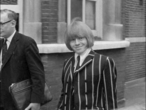 vídeos de stock e filmes b-roll de brian jones sent for trial on drugs charge when he appeared at west london court / jones leaves court surrounded by photographers and media. - rolling stones