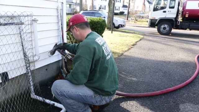 Brian Mantville owner of Veneto Sons Oil pumps oil into a house in Milton Massachusetts Worker unravels a hose from the back of a petrol truck and...