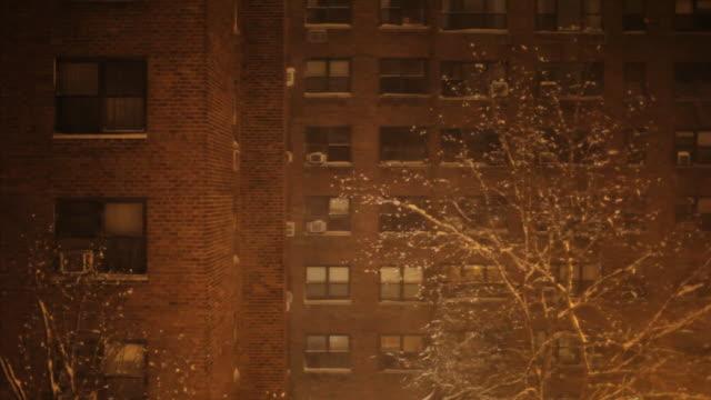 brick apartment building in snow - night