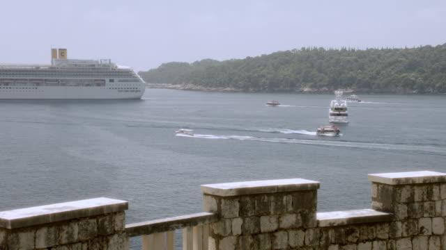 vídeos y material grabado en eventos de stock de pan brick balcony overlooking a hilly coastline along a waterway where boats are traveling near a cruise ship - pasear en coche sin destino