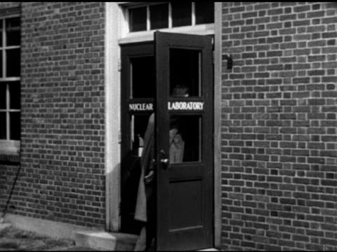 vídeos de stock, filmes e b-roll de brick building, men walking into 'nuclear laboratory', machine , unidentified professor working w/ student, sot talking about bombarding thorium,... - 1951