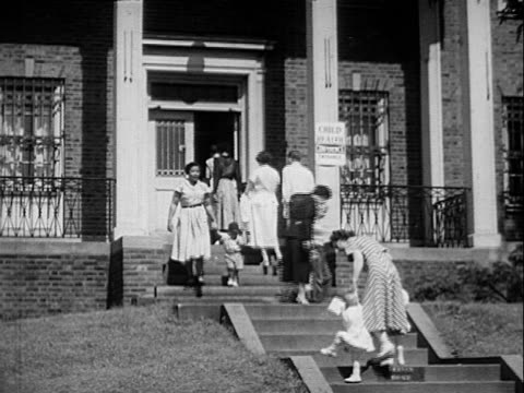 Brick building steps leading to porch parents walking with/or carrying babies children up/down stairs into/out of clinic