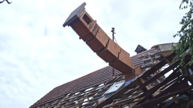 Brick chimney being pushed down the roof of the house being demolished by an excavator