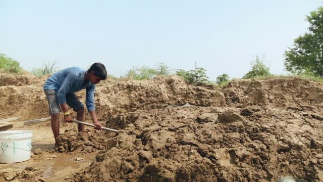 brick factory worker mixing clay, haryana, india - jäthacke stock-videos und b-roll-filmmaterial