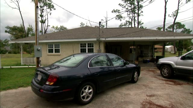 ws brick home w/ carport two cars parked in driveway fg pan ws fema trailer at edge of drive - trailer stock videos & royalty-free footage