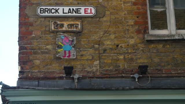 a brick lane street sign in both english and bengali - street style点の映像素材/bロール