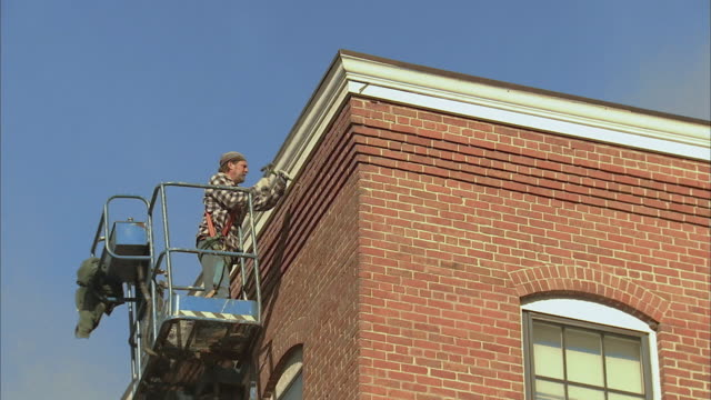ws la brick layer in cherry picker fixing brick on side of building / rutland, vermont, usa - cherry picker stock videos & royalty-free footage