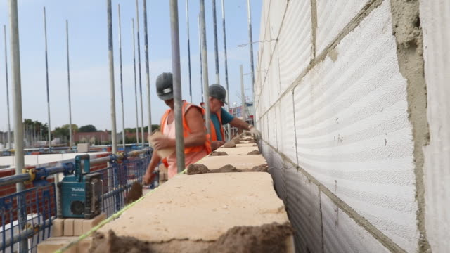 brick layers building wall at persimmon and charles church new housing construction site, in towcester, northamptonshire, u.k., england, on... - construction industry stock videos & royalty-free footage