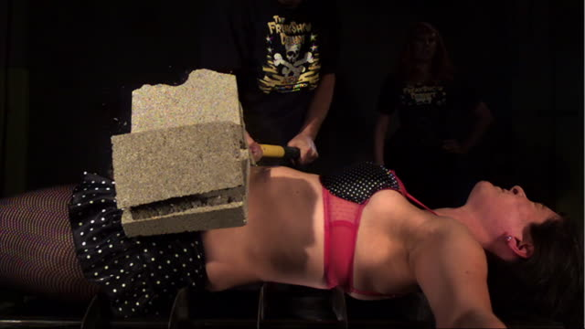 stockvideo's en b-roll-footage met a brick on a woman's stomach breaks as a man hits it with a hammer. - menselijke buik