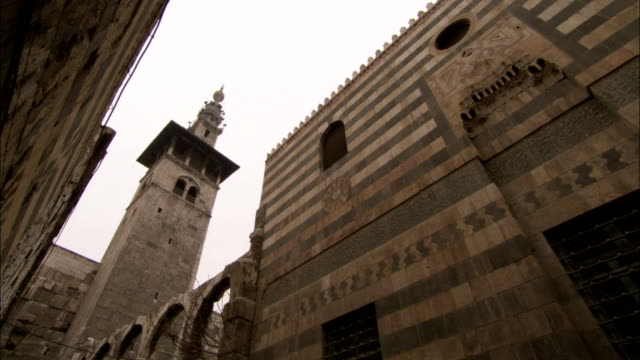 brick patterns and arches decorate the outside of a mosque in the old town of damascus. available in hd. - minareto video stock e b–roll
