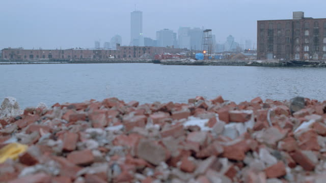 brick rubble lies on the riverbank with the world trade center on the distant skyline. - rubble stock-videos und b-roll-filmmaterial