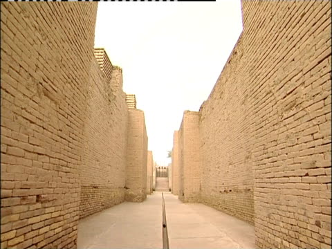 brick walls line a corridor in the ancient city of babylon. - babylon stock videos and b-roll footage