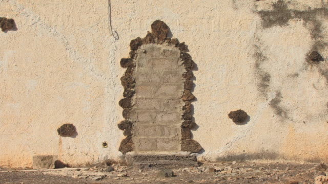 vídeos de stock e filmes b-roll de cu bricked-up doorway on side of house/ zo ms side of house/ fuerteventura, canary islands - cinza