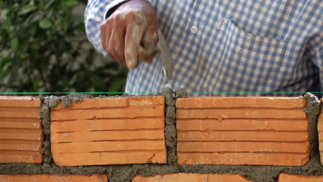 bricklayer construction brick wall, 4k - arranging stock videos and b-roll footage