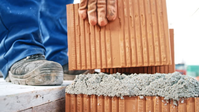 bricklayer laying a brick at the end of the line - brick stock videos & royalty-free footage