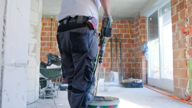 bricklayer mixing cement in a bucket - appliance stock videos & royalty-free footage
