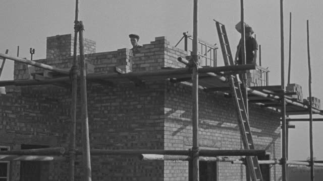 vídeos de stock e filmes b-roll de 1947 montage bricklayers building a residence with bricks / united kingdom - 1947