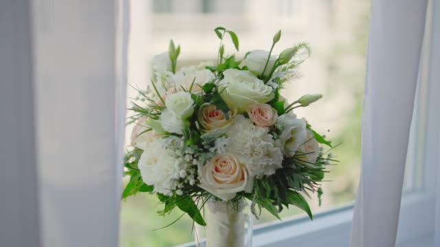 vídeos de stock e filmes b-roll de bridal bouquet with window in background - stock video - trílio