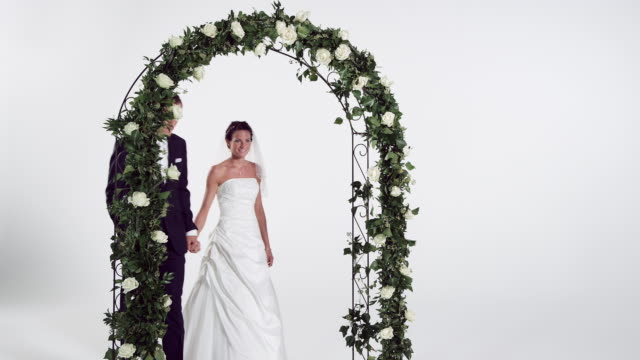bridal couple walking through archway - groom stock videos and b-roll footage