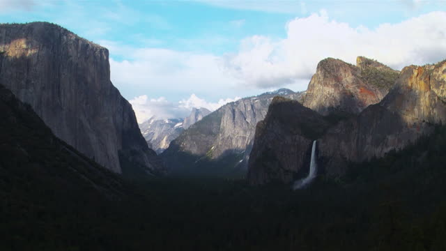 bridal veil falls pour over rugged cliffs in yosemite national park. - bridal veil falls yosemite stock videos & royalty-free footage