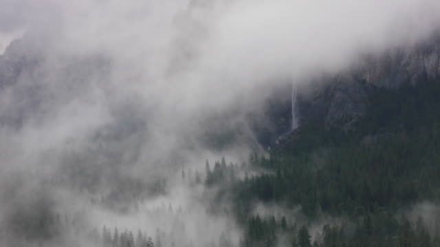 tl, ms of bridalveil fall with dramatic winter storm clouds in valley, yosemite valley in yosemite national park, california - bridal veil falls yosemite stock videos & royalty-free footage