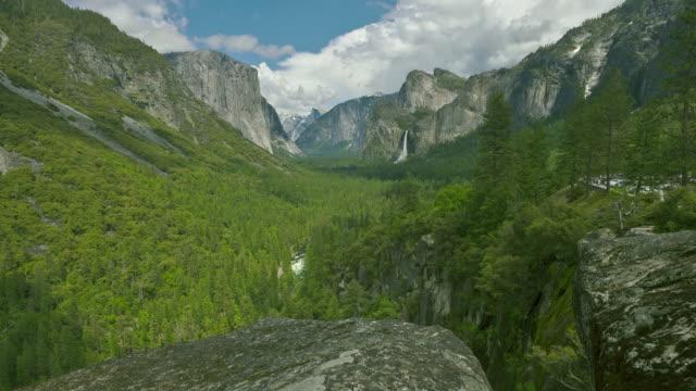 bridalveil falls cascades beyond a lush forest at california's yosemite valley. - bridal veil falls yosemite stock videos & royalty-free footage