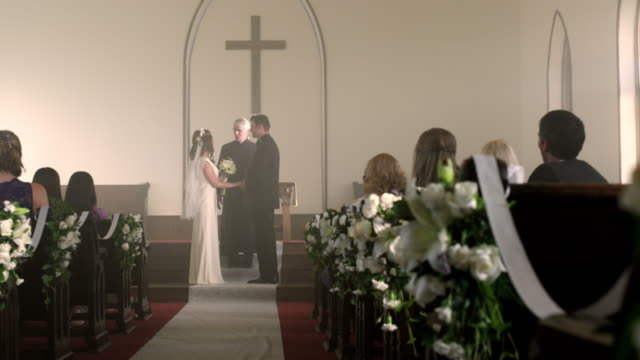 vidéos et rushes de bride and groom at the front of a chapel with a preacher. - prêtre