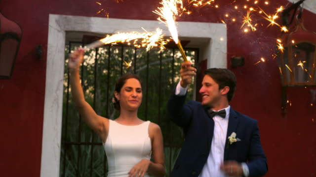 ms bride and groom celebrating with sparklers after cutting cake during outdoor wedding reception - biografi bildbanksvideor och videomaterial från bakom kulisserna