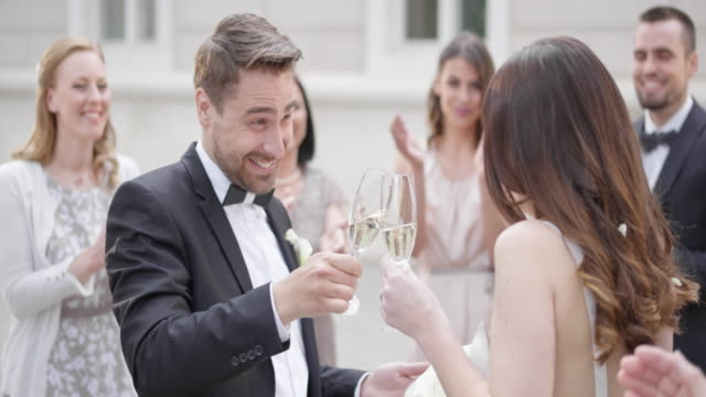 SLO MO Bride and groom clinking glasses after the wedding
