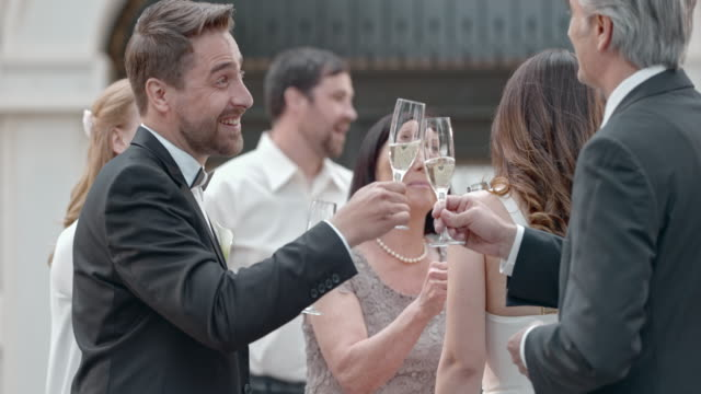 SLO MO Bride and groom clinking glasses with guests