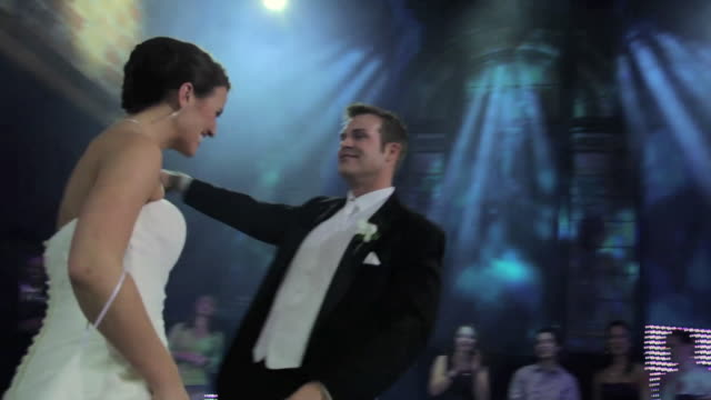 Bride and groom dance while surrounded by ring of clapping guests