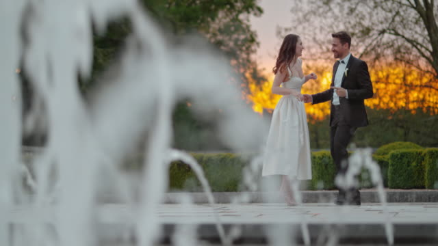 slo mo bride and groom dancing at sunset - fountain stock videos & royalty-free footage