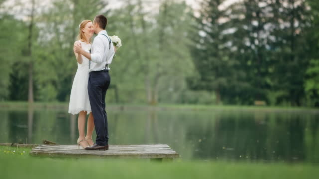 SLO MO Bride and groom dancing by the lake