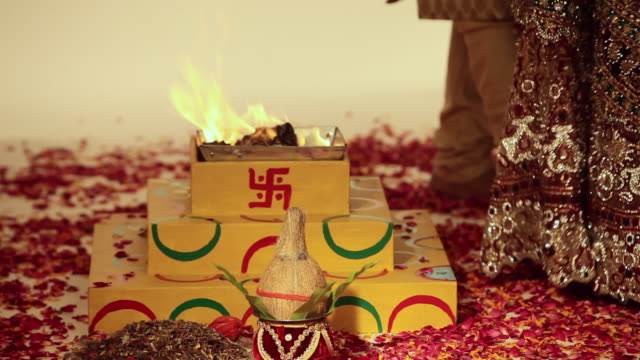 bride and groom doing phere around havan kund  - fire natural phenomenon stock videos & royalty-free footage