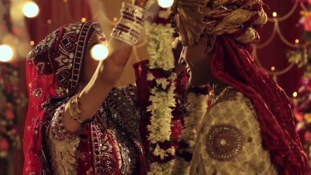 bride and groom doing varmala in the marriage  - indian ethnicity stock-videos und b-roll-filmmaterial