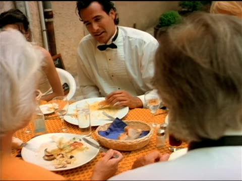 A bride and groom enjoy their wedding dinner, and the bride shows her rings to another woman.