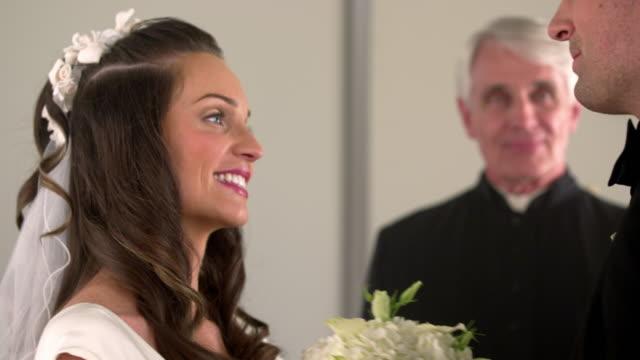 vídeos de stock, filmes e b-roll de bride and groom facing each other as the preacher talks to them. - batom rosa