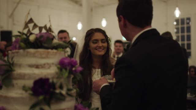 Bride and groom feeding cake to each other at wedding reception / Provo, Utah, United States
