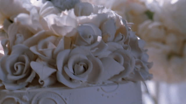 A bride and groom figurine adorn the top of an ornate white wedding cake.