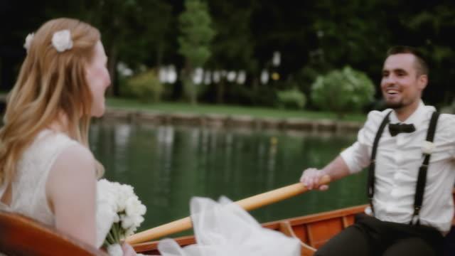 slo-mo-braut und bräutigam spaß in einem boot - suspenders stock-videos und b-roll-filmmaterial