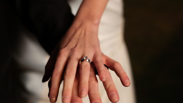 HANDHELD CLOSE UP bride and groom hold hands outdoors at night