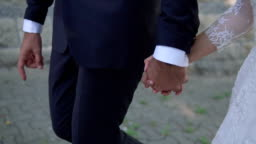 Bride and groom holding hands and walking