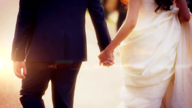 Bride and groom holding hands during walking in park.