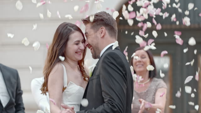 SLO MO Bride and groom in a rose petal shower