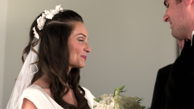 vidéos et rushes de bride and groom kiss and smile at their wedding ceremony. - vêtement religieux