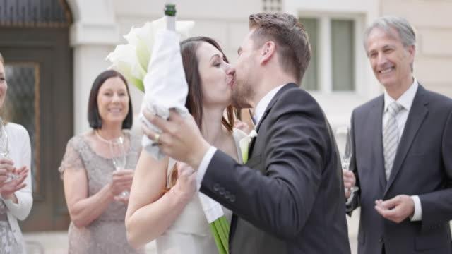vidéos et rushes de slo mo mariée et le marié s'embrasser après avoir ouvert une bouteille de vin mousseux - jeunes mariés