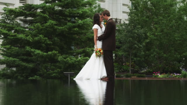 ws tu bride and groom kissing by pond / salt lake city, utah, usa - face to face stock videos & royalty-free footage