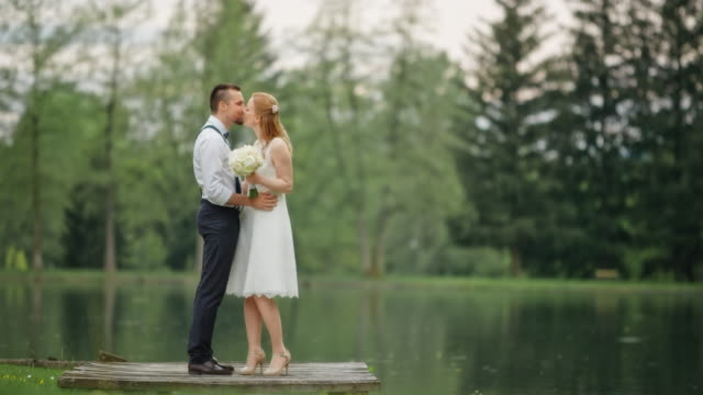 slo mo bride and groom kissing by the lake - heterosexual couple stock videos & royalty-free footage
