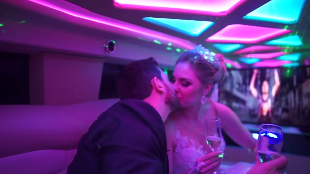 bride and groom kissing in limousine on their way to their wedding party - limousine stock videos & royalty-free footage